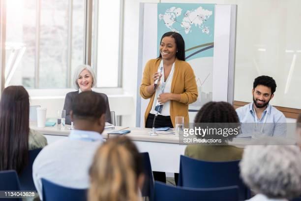 a mulher de negócios alegre do americano africano fala durante o seminário - painel de discussão - fotografias e filmes do acervo