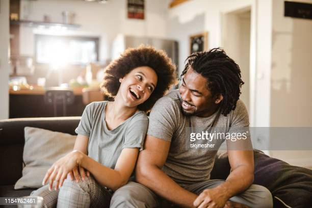 cheerful african american couple communicating in the living room. - black couple stock pictures, royalty-free photos & images