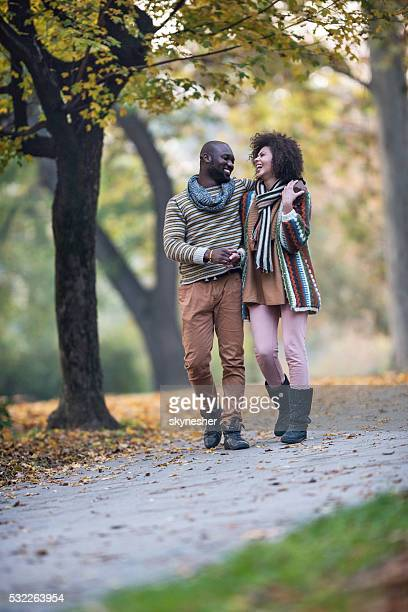 Cheerful African American couple walking embraced in autumn park.