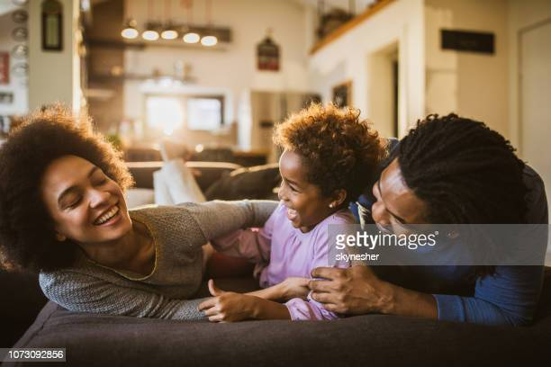 cheerful african american family having fun on sofa at home. - tickling stock pictures, royalty-free photos & images