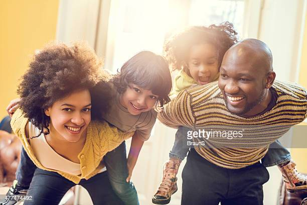 Cheerful African American family piggybacking at home.