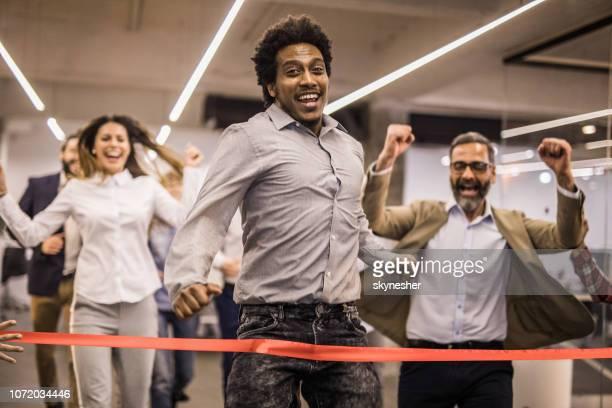 alegre freelancer afro-americano a ganhar na corrida de esportes no escritório casual. - linha de chegada - fotografias e filmes do acervo