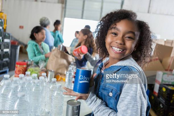 Cheerful African American girl collects money during food drive