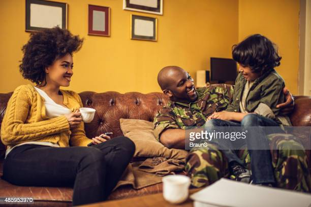 Cheerful African American military family having fun together at home.