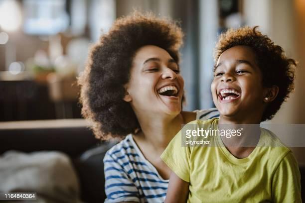matriz e filha alegres do americano africano em casa. - rindo - fotografias e filmes do acervo
