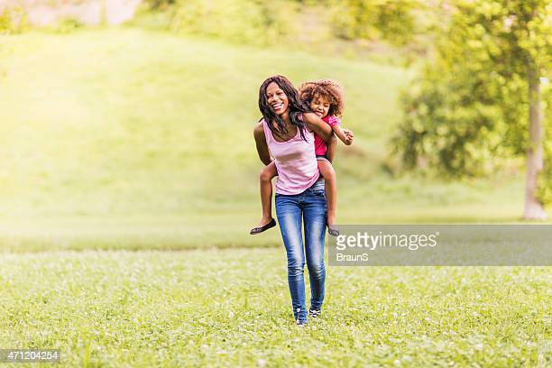 Cheerful African American mother and daughter piggybacking outdoors.