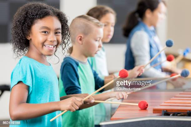 cheerful african american schoolgirl plays marimba - percussion instrument stock photos and pictures