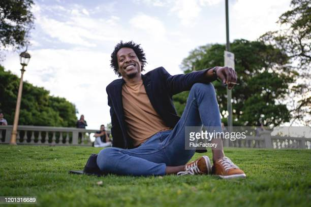cheerful african american smoking a cigarette at a park - suave stock pictures, royalty-free photos & images
