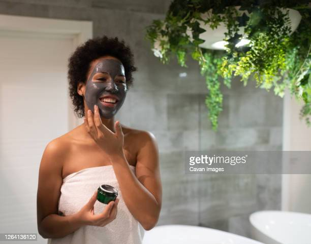 cheerful african american woman applying mask - indulgence stock pictures, royalty-free photos & images
