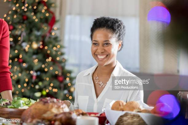 cheerful african american woman enjoys christmas dinner celebration - one mid adult woman only stock pictures, royalty-free photos & images