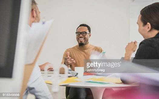 Cheerful African business professional with goatee and glasses smiling in meeting