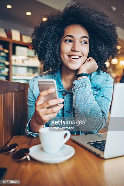Cheerful African ethnicity girl with smart phone