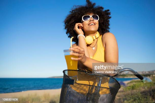 cheerful african woman drinking yellow cocktail on beach - yellow dress stock pictures, royalty-free photos & images