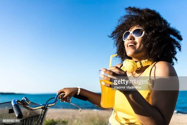 Mujer africana alegre bebida cóctel amarillo en la playa