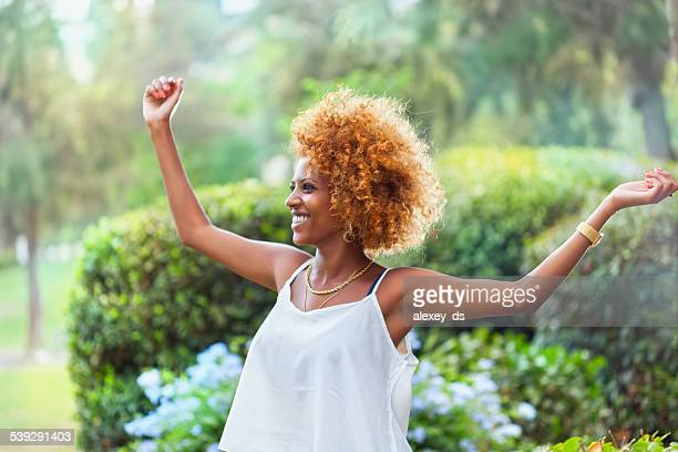 Cheerful African woman standing her hands up. Outdoors