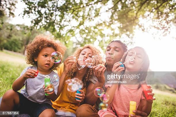 Joyeuse famille afro-américaine et bulles de soufflage de liens