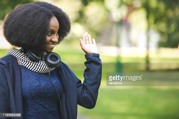 cheerful african-american woman saying hi to a friend in a city park - mmeemil stock photos and pictures
