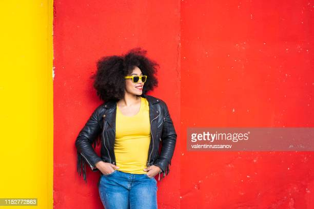 cheerful afro women standing together and smiling on colorful backgraund - colorful background stock photos and pictures