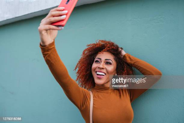 cheerful afro young woman taking selfie with smart phone while standing by wall - コイリーヘア ストックフォトと画像