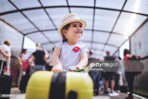 cheerful and excited toddler with her coffer on a airport - luggage stock pictures, royalty-free photos & images