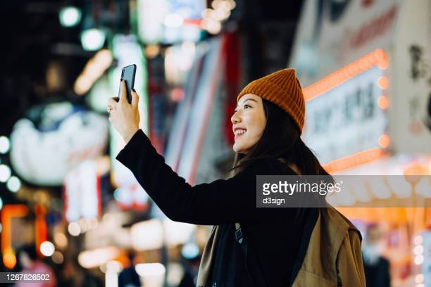 cheerful and stylish young asian female traveller with backpack taking a selfie with smartphone while exploring and strolling in busy downtown city street at night in osaka, japan - 女性 ストックフォトと画像
