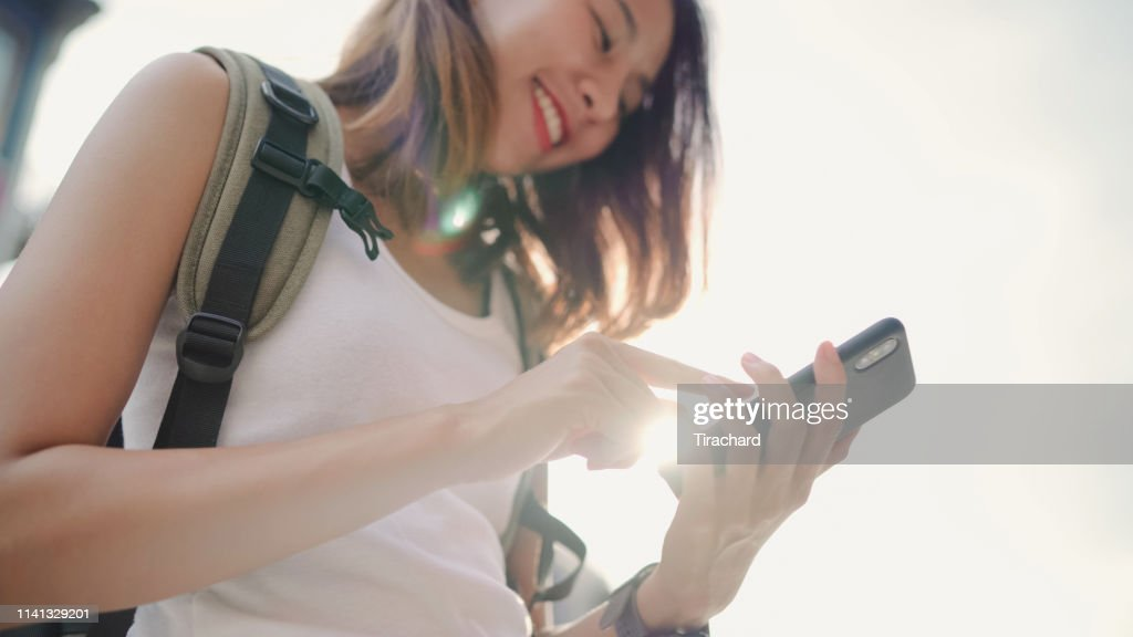 Cheerful Asian backpacker blogger woman using smartphone for direction and looking on location map while traveling at Chinatown in Beijing, China. Lifestyle backpack tourist travel holiday concept. : Stock Photo