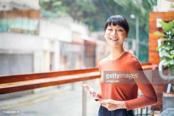alegre empresaria asiática sosteniendo una tableta digital - businesswear fotografías e imágenes de stock