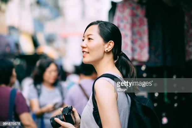 cheerful asian female traveller carrying camera visiting and exploring streets of hong kong - fashion hong kong stock photos and pictures
