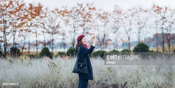cheerful asian female traveller taking photos of beautiful scenics with smartphone in a nature park - capturing an image stock pictures, royalty-free photos & images