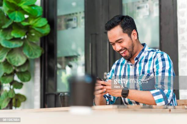 cheerful asian man using cell phone - south east asian ethnicity stock pictures, royalty-free photos & images