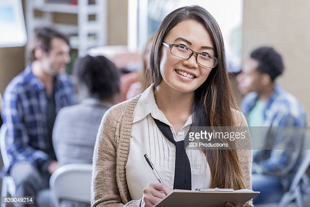 Cheerful Asian psychologist takes notes before counseling session