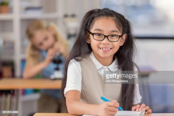 Cheerful Asian schoolgirl in classroom