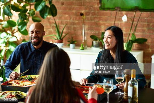 cheerful asian woman and african american man at dinner party laughing - dinner party stock pictures, royalty-free photos & images