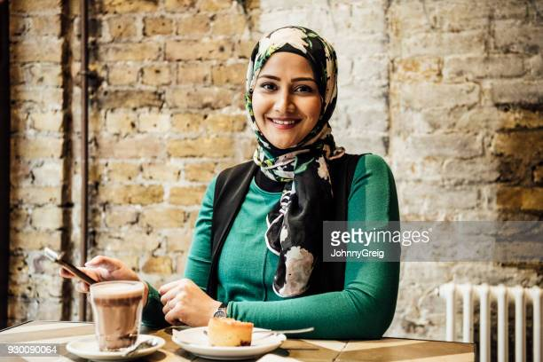 Cheerful Asian woman in cafe with phone and hot drink smiling