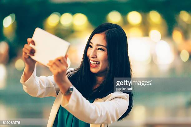 Cheerful asian woman making selfie with digital tablet on street