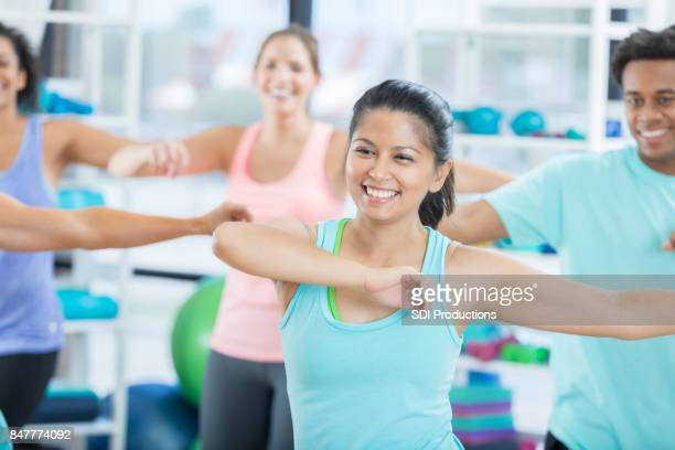 Cheerful Asian woman swings her arms in dance class at gym