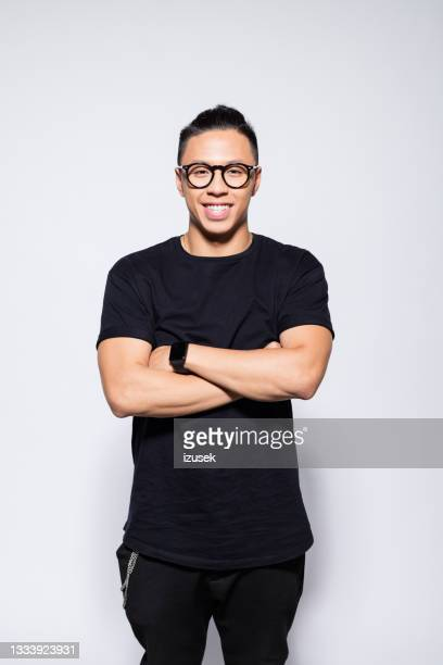 cheerful asian young man in black clothes - izusek stock pictures, royalty-free photos & images