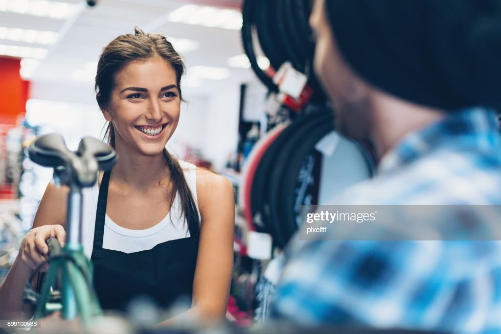 Cheerful assistant in a bike shop : Stock Photo