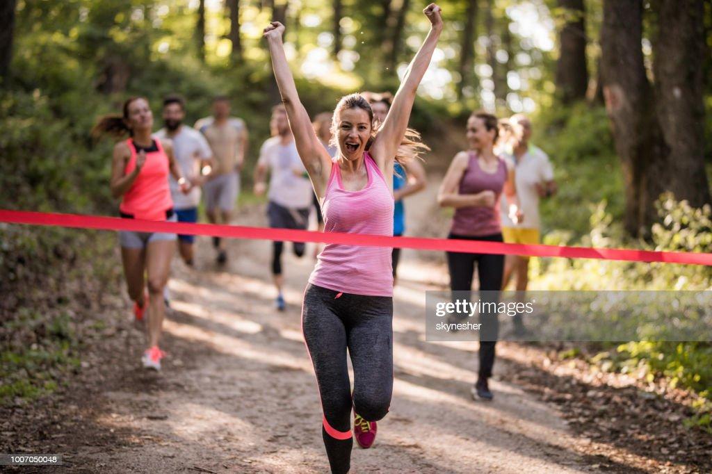 Fröhliche sportliche Frau schreien, während die Marathonrennen im Wald zu gewinnen. : Stock-Foto