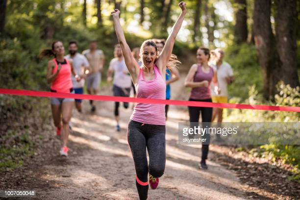 cheerful athletic woman screaming while winning the marathon race in the forest. - finish line stock pictures, royalty-free photos & images