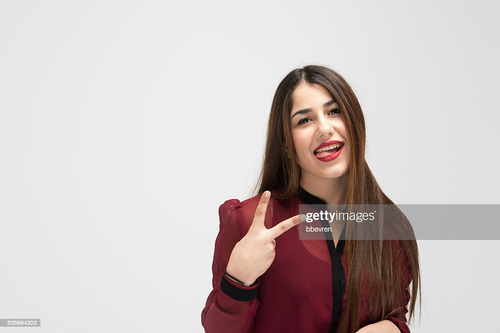 Cheerful attractive girl making victory sign while shpwing her t : Stockfoto
