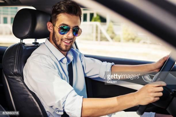 Cheerful attractive man driving car