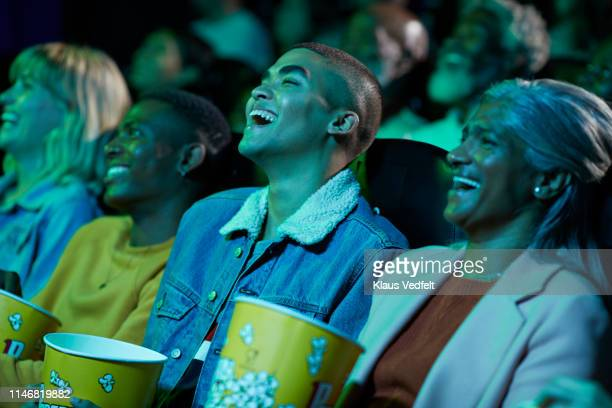 cheerful audience enjoying comedy movie - blue film video stock pictures, royalty-free photos & images