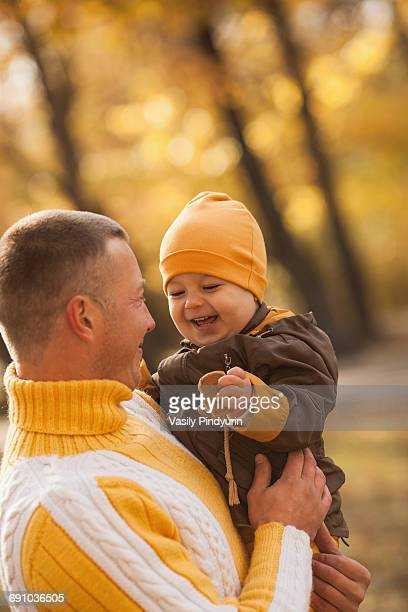 Cheerful baby boy being carried by father at park during autumn