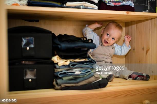 Cheerful baby boy inside the closet