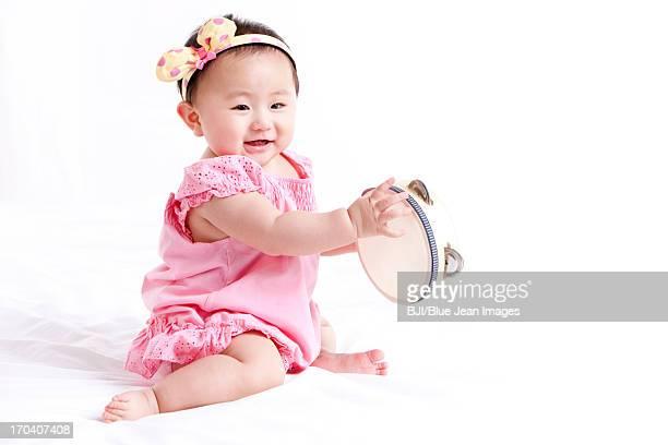 Cheerful baby girl with tambourine