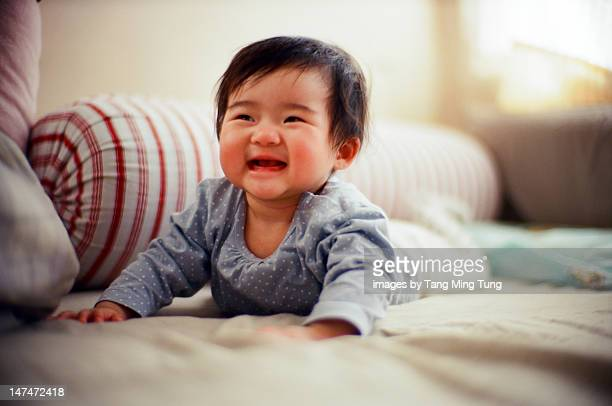 Cheerful baby laughing on bed