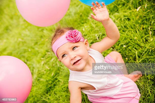 Cheerful Baby on grass playing with pink balloons
