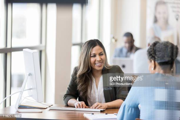 cheerful bank employee opens new account for client - bank manager stock pictures, royalty-free photos & images