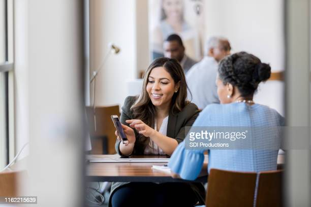 cheerful bank employee shows customer banking app - cheerful stock pictures, royalty-free photos & images